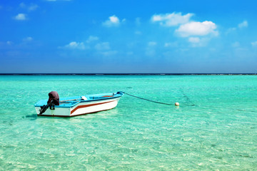 Shoreline of a tropical island with boat in the Maldives and vie