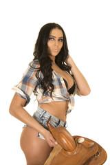 cowgirl short denim shorts holding saddle in hand