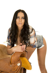 cowgirl short denim shorts lean on saddle looking very serious