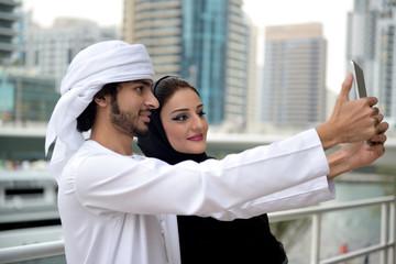 Young Emirati arab couple taking photo