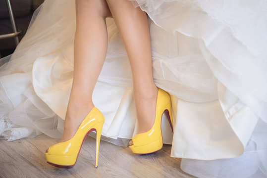 Bride legs and yellow wedding shoes