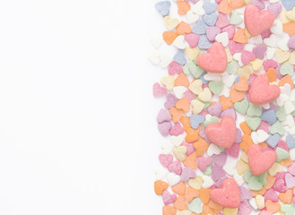 Background on Valentine's Day. Colorful sprinkling sugar confectionery and biscuits shaped heart. Empty space for text. White background.