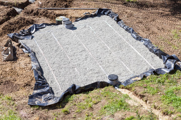 Aerial view of a new gravel filter bed for a septic tank for disposal of domestic wastewater and sewage showing the pipes, filter and pump