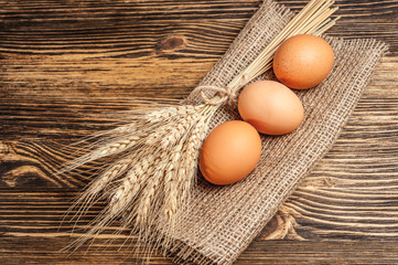 there are three eggs on sackcloth with wheat spica