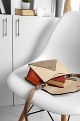 Fashion female handbag with book on white chair