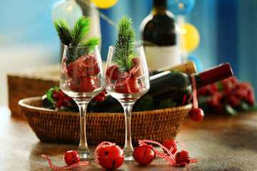 Wine in wicker bowl and Christmas decor on table