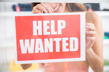 Owner Holding Help Wanted Sign In Retail Store