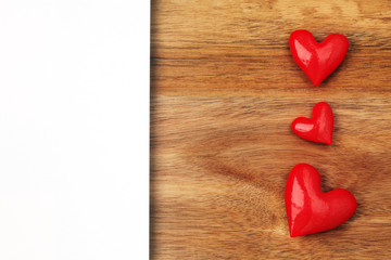 Shiny red hearts on wooden background