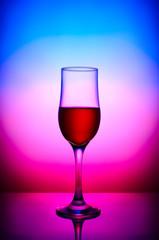 Red wine glass in blue magenta gradient background