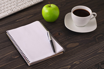 Open notepad with pen, coffee, apple and computer keyboard