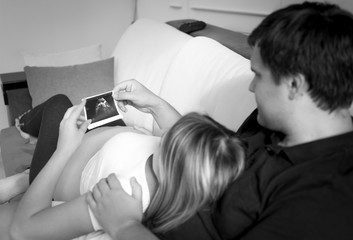 Black and white portrait of couple waiting for baby looking on f