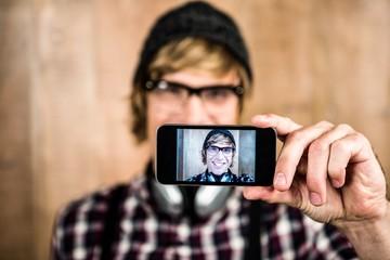 Smiling blond hipster taking selfie