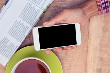 Man using smart phone by coffee and newspaper on table