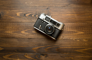 manual camera lying on old wooden background