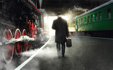 man in bowler hat with suitcase walking on the platform next to