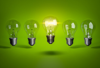 Glowing bulb in row of light bulb on green background