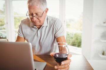 Focused senior man using laptop and drinking wine