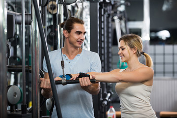 Adults having strength training under coach control in gym