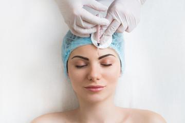 Frau erhält kosmetische Spritze in die Stirn