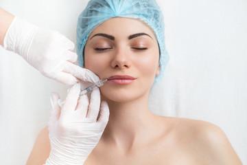 Frau erhält kosmetische Spritze in die Lippen