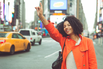 American woman calling a taxi in Time square