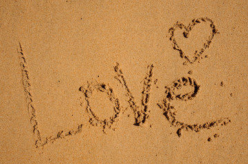 Love word drawn on beach sand