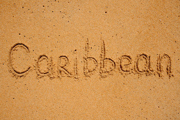 The word Caribbean is written on sand background