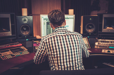 Sound engineer working at mixing panel in the boutique recording