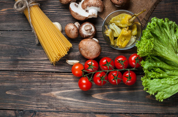 Pasta, tomatoes, salad, pepper, mushrooms and book of recipes on wooden table background