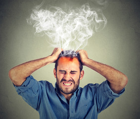 Stressed man having headache steam coming up isolated on gray wall background