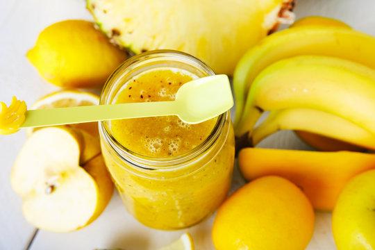 Fresh organic yellow smoothie with banana, apple, mango, pear, p