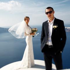 Romantic beautiful couple posing on terrace with sea, islands an