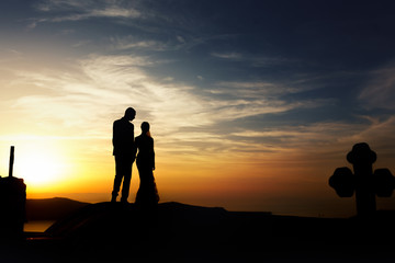 Groom and bride silhouette kissing on church roof at sunset sky