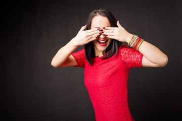 Woman on black background covering her eyes with both hands