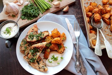 Roasted chicken fillet in herbs with fried potatoes and garlic sauce