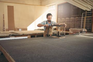 Carpenter making a display case in his workshop