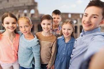 children talking selfie over coliseum in rome