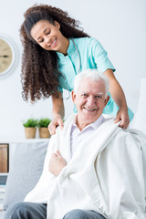 Nurse supporting ill old man