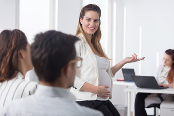 Pregnant woman during business meeting