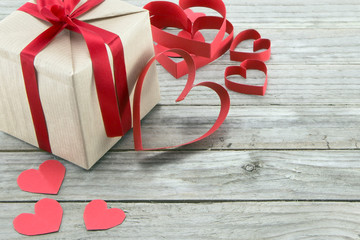 Red hearts and present on a wood background