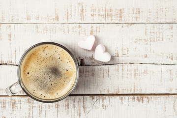 hot morning coffee with two heart shaped мarshmallows on white
