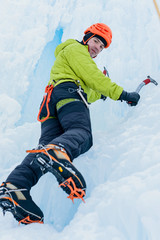 Athletic alpinist man in orange helmet and ice tools axe climbing a large wall of ice. Outdoor Sports Portrait