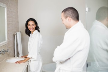 Smiling couple in bathrobe looking at mirror