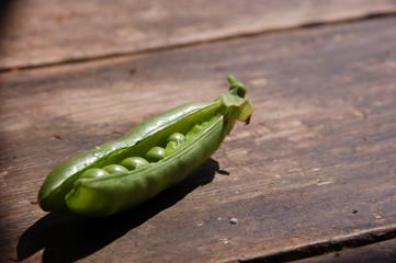 Fresh peas on wooden farm table
