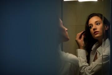 Beautiful brunette applying mascara