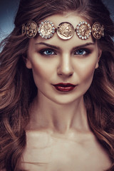Beautiful young blonde woman with long hair with a diadem in the Greek style
