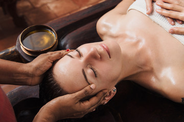 Ayurvedic face massage with oil on the wooden table