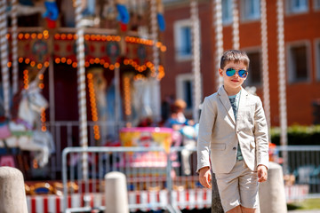 Stylish kid in a nice suit and glasses near the traditional French merry-go-round