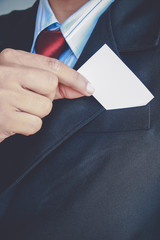 Businessman showing paper on gray background,Vintage tone style.
