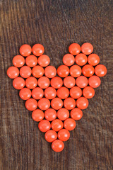 Heart of vitamins, vital heart for Valentines Day on wooden background.